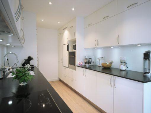Cuisine d'artisan dans un appartement de Lyon 3° meubles blancs, et plan de travail en marbre noir.