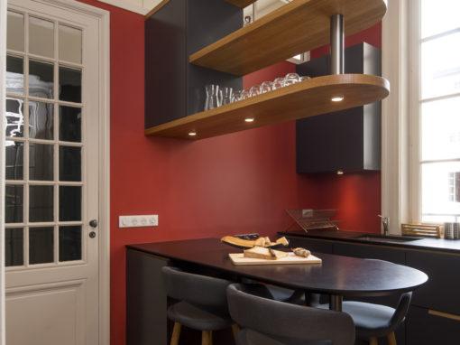 Cuisine d'artisan dans un appartement de Lyon 3° meubles blancs, et plan de travail en granit noir.